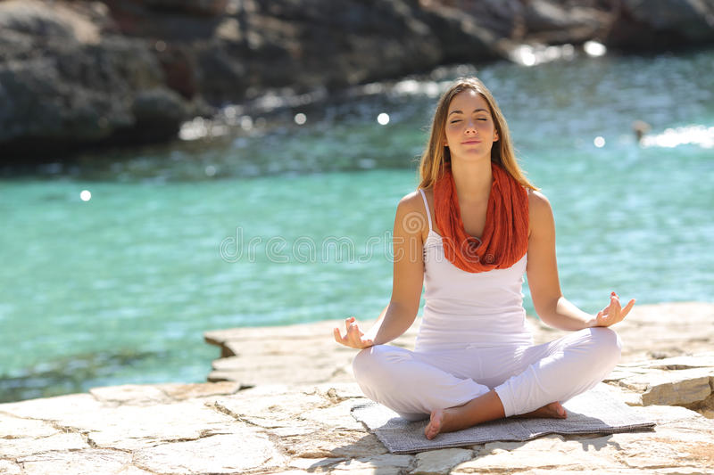 Relaxed girl doing yoga exercises on holidays. In a tropical beach royalty free stock photo
