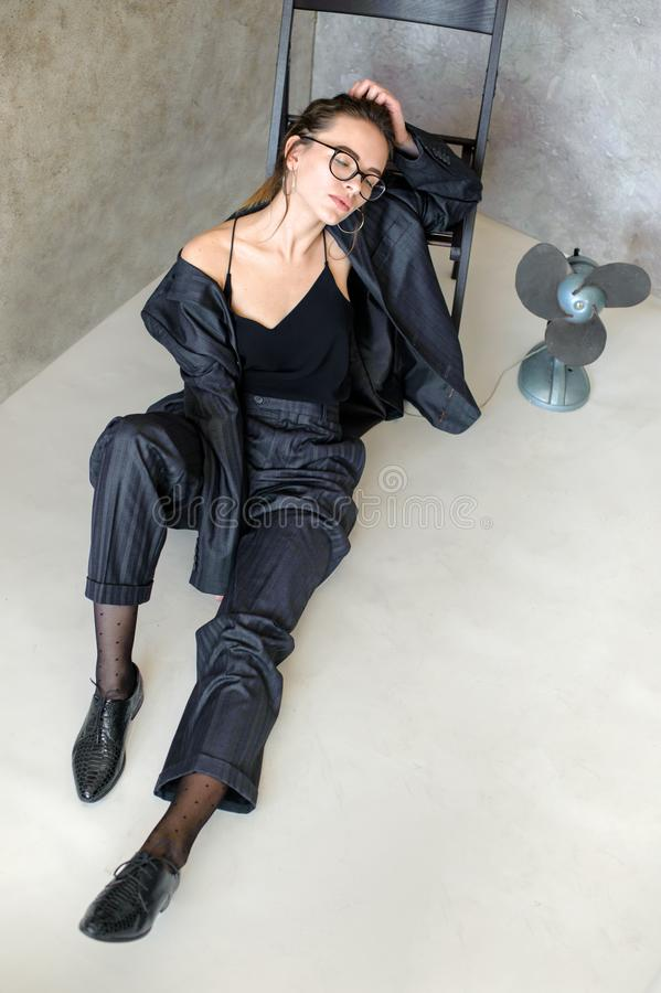 Relaxed girl in glasses, jacket on body, sits on floor near retro style fan royalty free stock photography