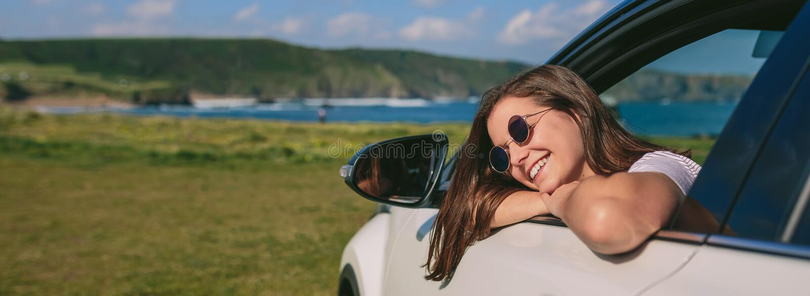 Girl leaning on window of the car royalty free stock photo