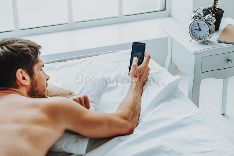 Relaxed guy checking mobile phone in morning stock photo