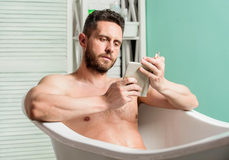 Relaxed guy reading book while relaxing in hot bath. Relax at home. Total relaxation. Personal hygiene. Nervous system royalty free stock photos