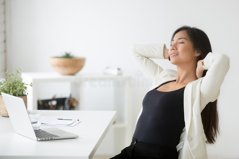 Relaxed happy asian woman enjoying break at workplace breathing royalty free stock photos