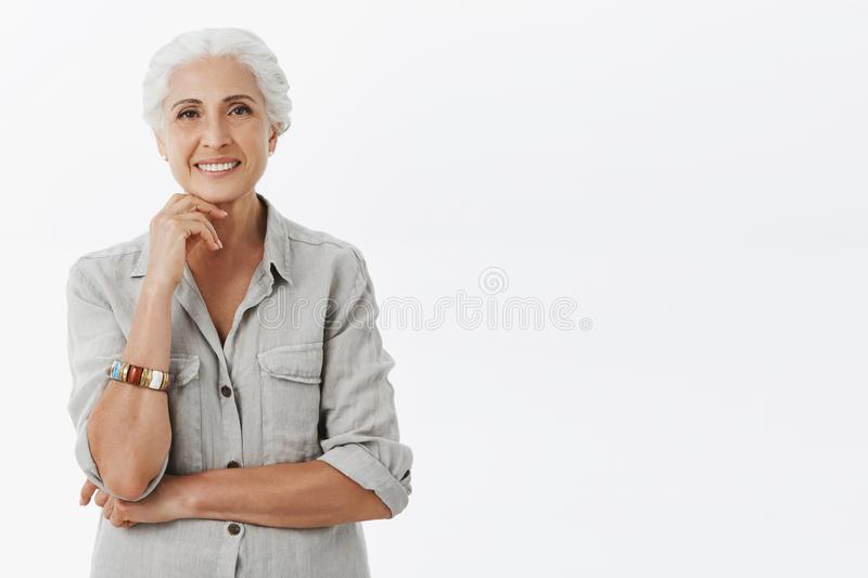 Relaxed and happy charming old lady with grey hair in casual shirt and bracelet leaning head on fist above chin smiling royalty free stock photo