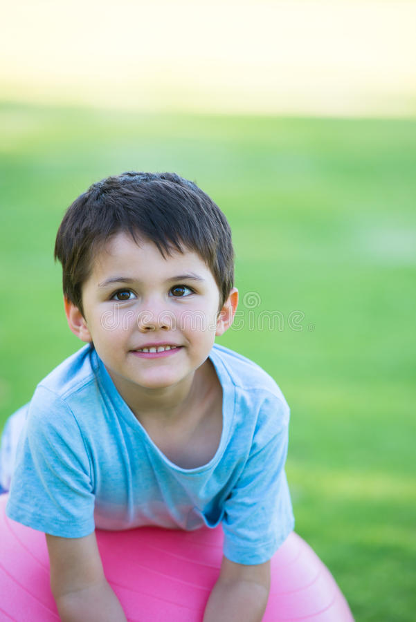 Relaxed happy hispanic boy portrait outdoor. Portrait young cute hispanic boy happy relaxed friendly smiling, leaning on pink exercise ball outdoor, blurred stock photography