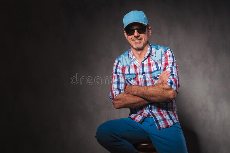 Relaxed happy old casual man sitting with hands crossed stock photos