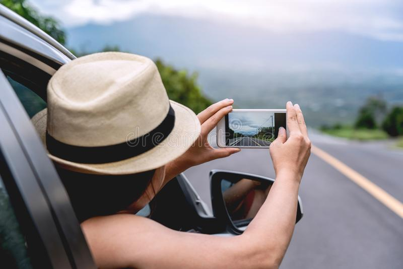 Relaxed happy traveler, Young beautiful girl wearing white hat weave Reach out of the car and using smart phone take photo at stock photography
