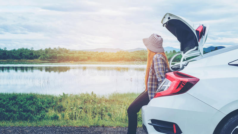 Relaxed happy woman traveler on summer roadtrip vacation on hatchback car royalty free stock images