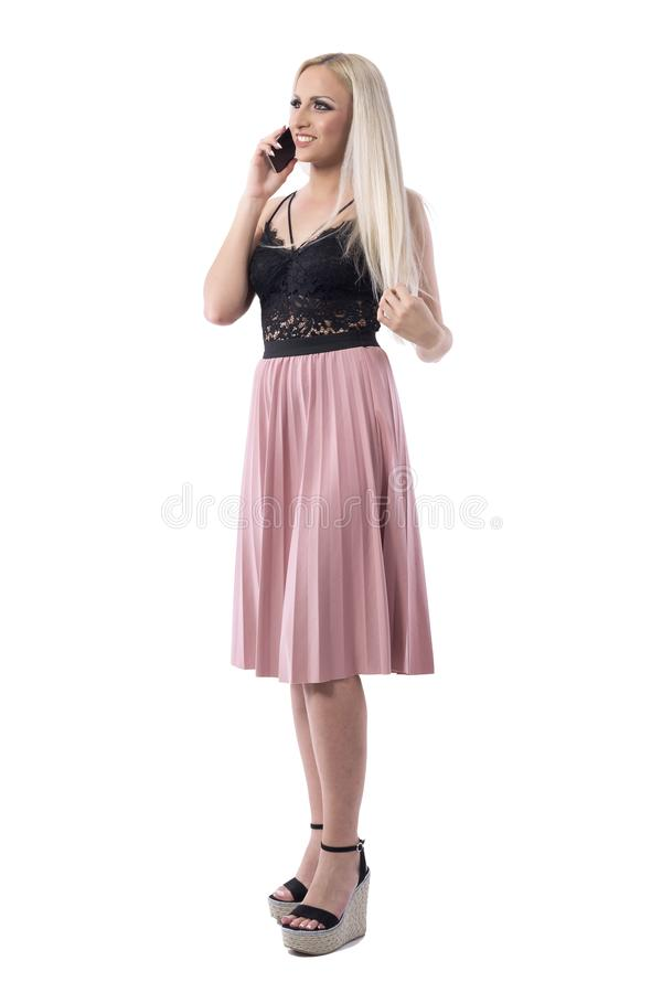 Relaxed happy young woman in elegant clothes talking on the phone smiling and having chit chat stock photo