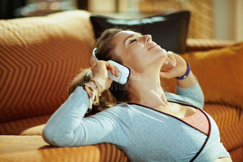 Sports woman listening to music with headphones in modern house. Relaxed healthy sports woman in fitness clothes listening to the music with headphones in the royalty free stock photos