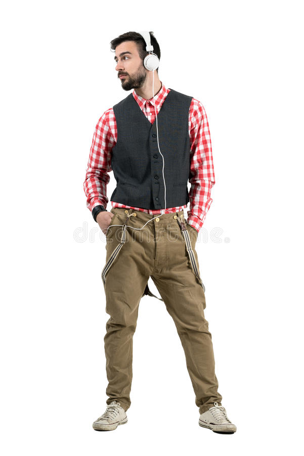 Relaxed hipster with hands in pocket listening mp3 player looking away royalty free stock photography