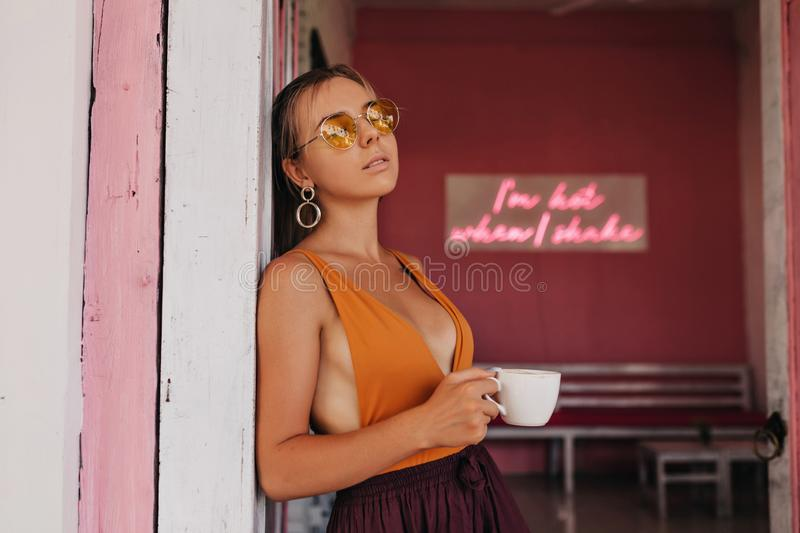 Relaxed lady in good mood playfully posing on bright cafeteria in warm weather. royalty free stock photo