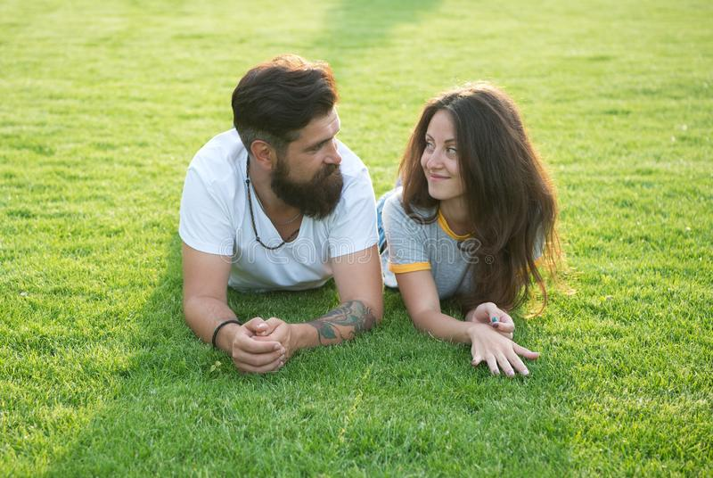 Relaxed and in love. Couple relaxing on grass enjoying each other. Man bearded hipster and pretty woman in love. Summer. Vacation. Fall in love. Summertime royalty free stock images