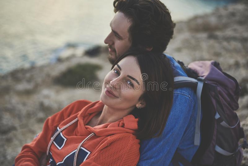 Relaxed loving couple enjoying ocean view. I am really happy. Portrait of glad young women looking at camera and smiling. Man is hugging her with love while royalty free stock photos