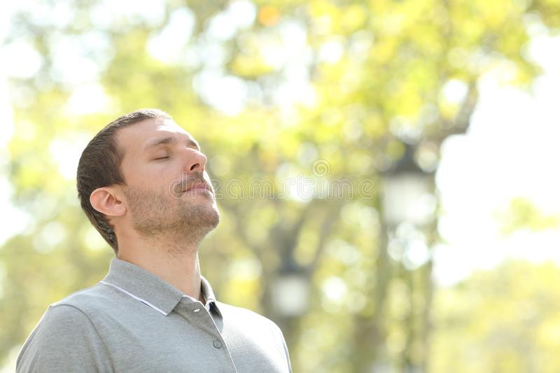 Relaxed man breathing deeply fresh air outside in a park royalty free stock photography
