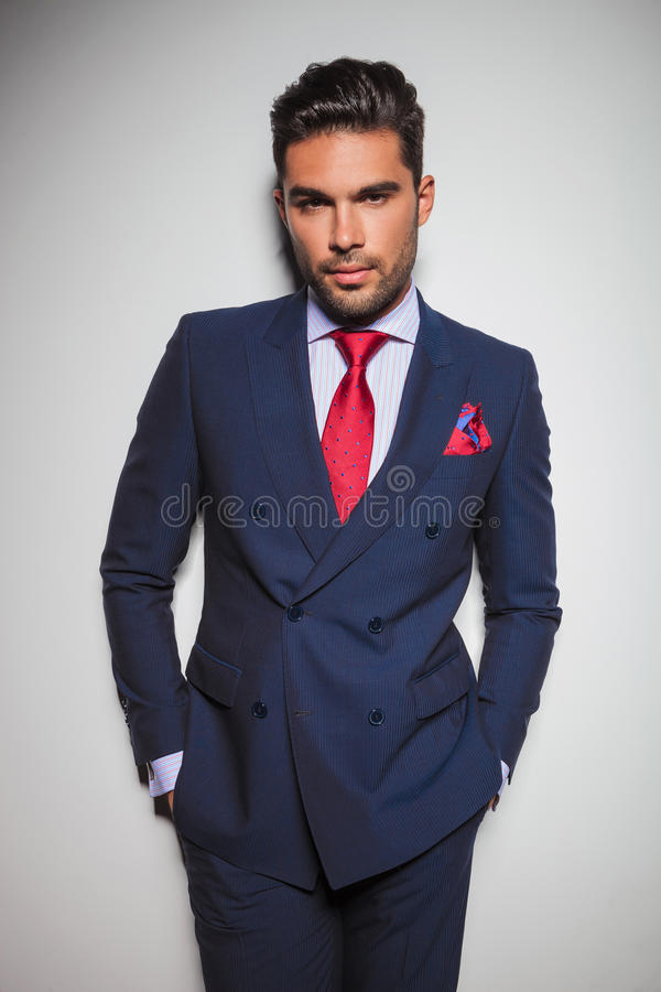 Relaxed man in double breasted suit with hands in pockets royalty free stock images