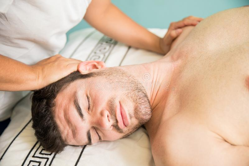 Relaxed man getting a neck massage. Closeup of a handsome Latin men getting a massage on his neck while relaxing in a health spa royalty free stock images