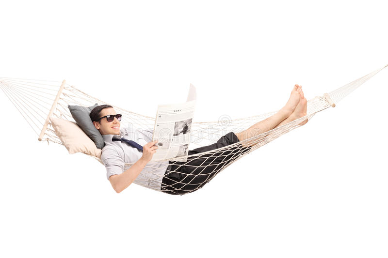 Relaxed man reading newspaper in a hammock. Relaxed young man reading a newspaper and lying in a comfortable hammock isolated on white background stock image