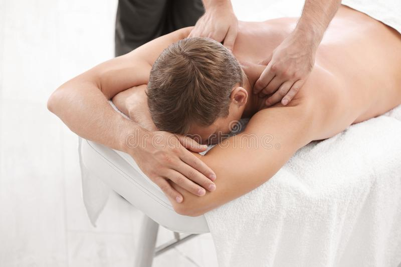 Relaxed man receiving back massage. In wellness center royalty free stock photography