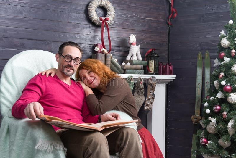 Relaxed man sitting in armchair and his wife leaning to him. Calm bearded men reading newspaper in the armchair and smiling while his loving wife putting her stock photos