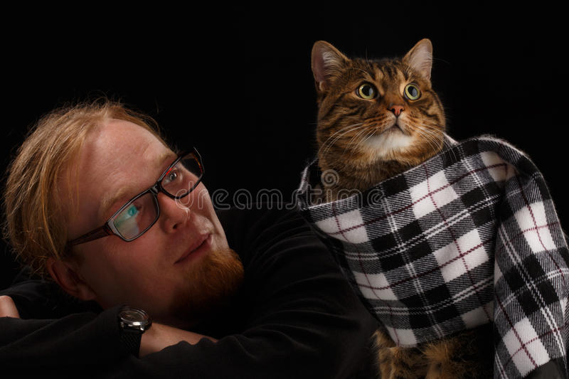 Relaxed man sitting with cat in his scarf. Shallow DOF. stock photos