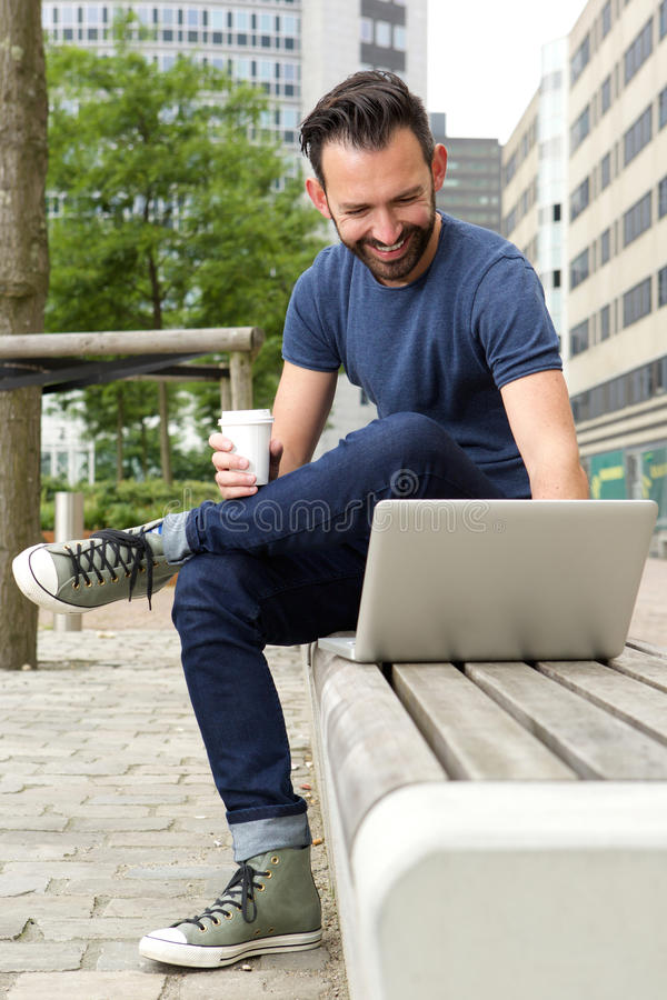 Relaxed man sitting outdoors and working on laptop royalty free stock photo
