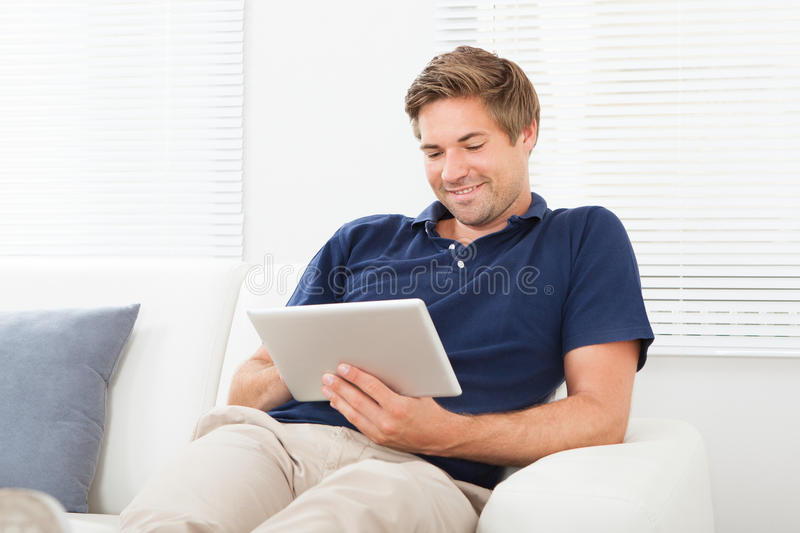 Relaxed man using digital tablet in living room royalty free stock photo