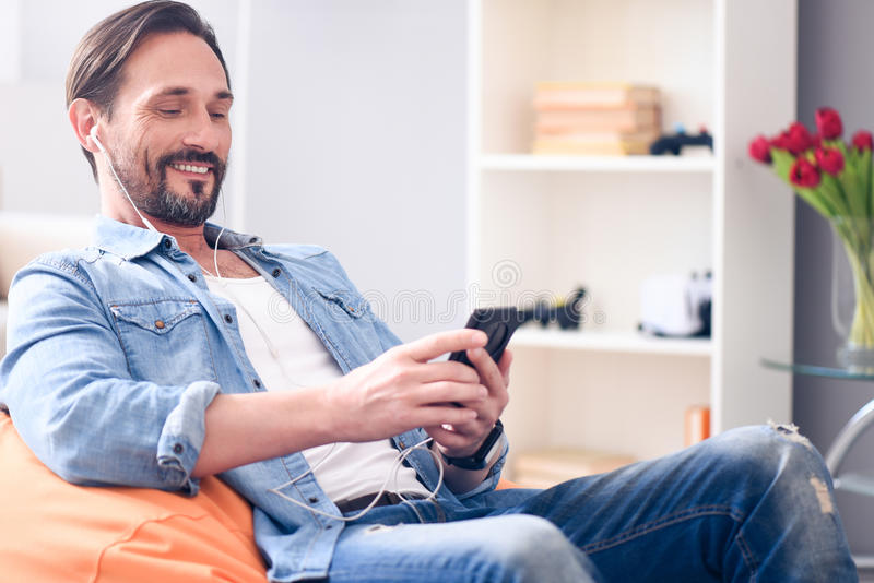 Relaxed man using earphones and smart phone stock images