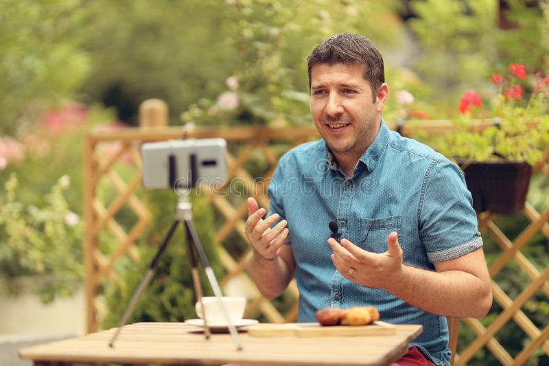 Relaxed manager discussing business strategies with his team on video call. Young casual business owner at a table having a video royalty free stock images