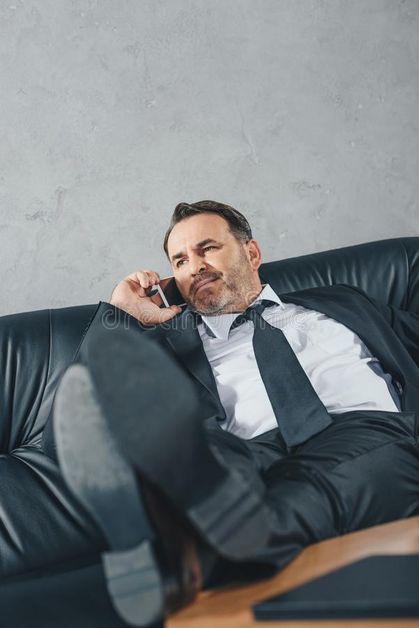 relaxed mature businessman talking by phone while sitting stock photos