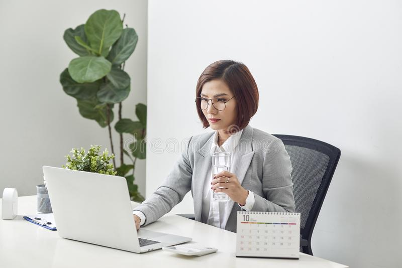 Relaxed mature businesswoman holding glass of water and working on her laptop in the office stock photography