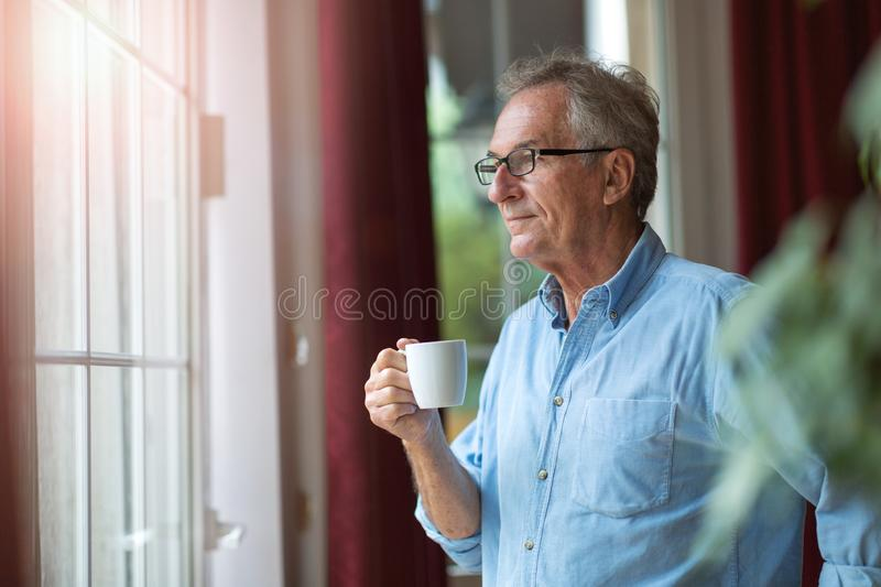 Relaxed mature man at home standing by the window royalty free stock photos