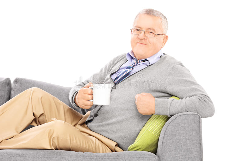 Relaxed mature man laying on sofa and drinking tea royalty free stock photo