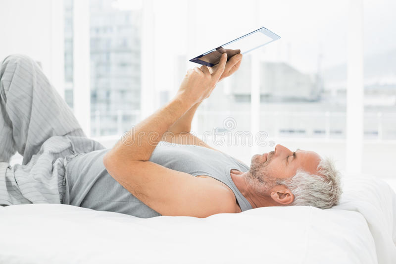 Relaxed mature man using digital tablet in bed stock photos