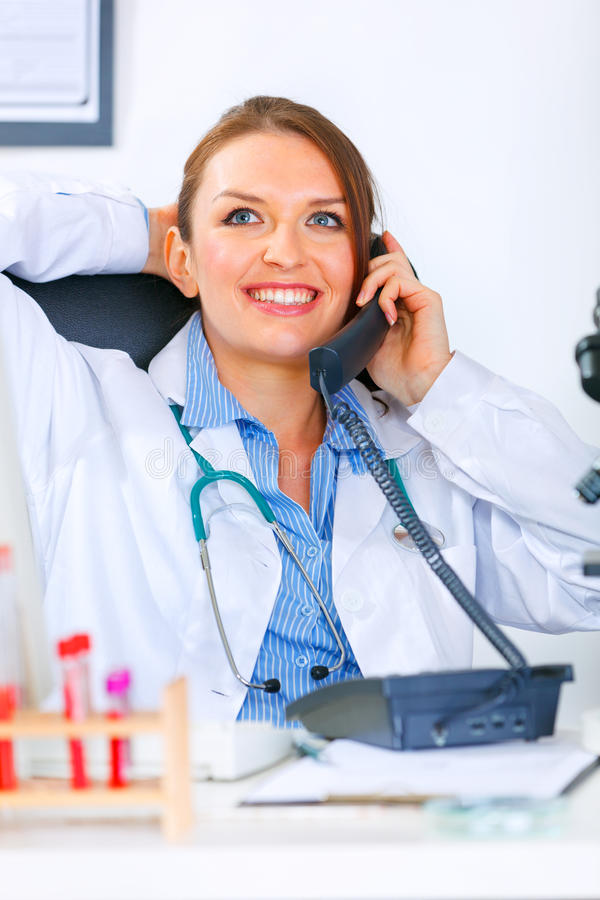 Relaxed medical doctor woman talking on phone. Relaxed medical doctor woman sitting at office table and talking on phone royalty free stock images
