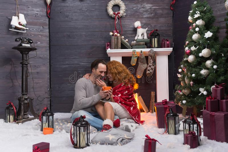 Romantic couple hugging and drinking tea while sitting near the fireplace. Relaxed middle aged couple enjoying New Year holidays and smiling while drinking tea royalty free stock photography