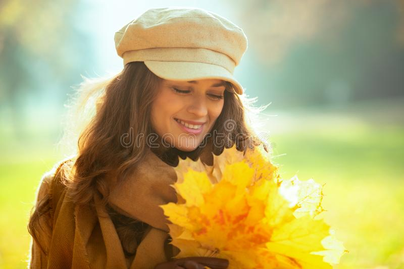 Relaxed modern woman with yellow leaves outside in autumn park royalty free stock photography