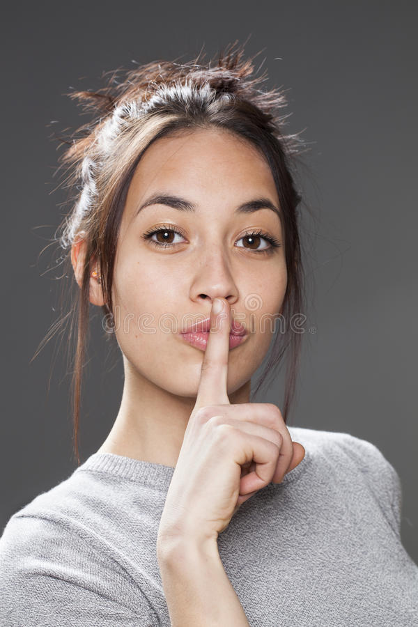 Relaxed multi-ethnic girl asking to keep quiet for discretion royalty free stock images