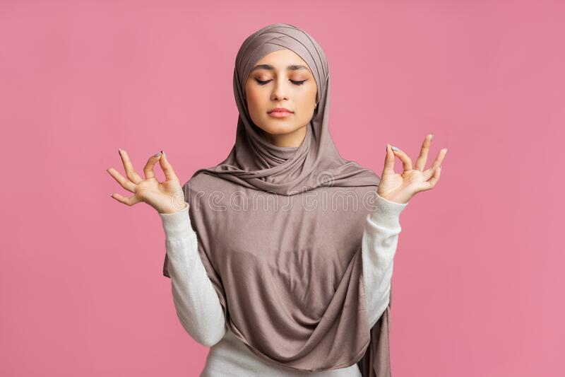 Relaxed muslim girl in hijab meditating over pink background stock images