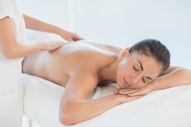 Relaxed naked woman receiving back massage royalty free stock photography