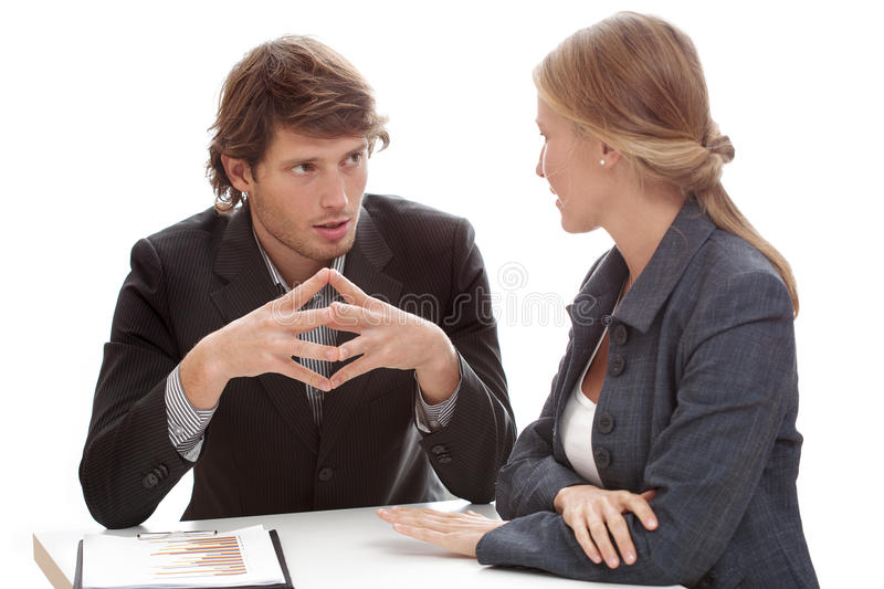 Relaxed office conversation. A relaxed conversation of a men and a women in the office stock photo
