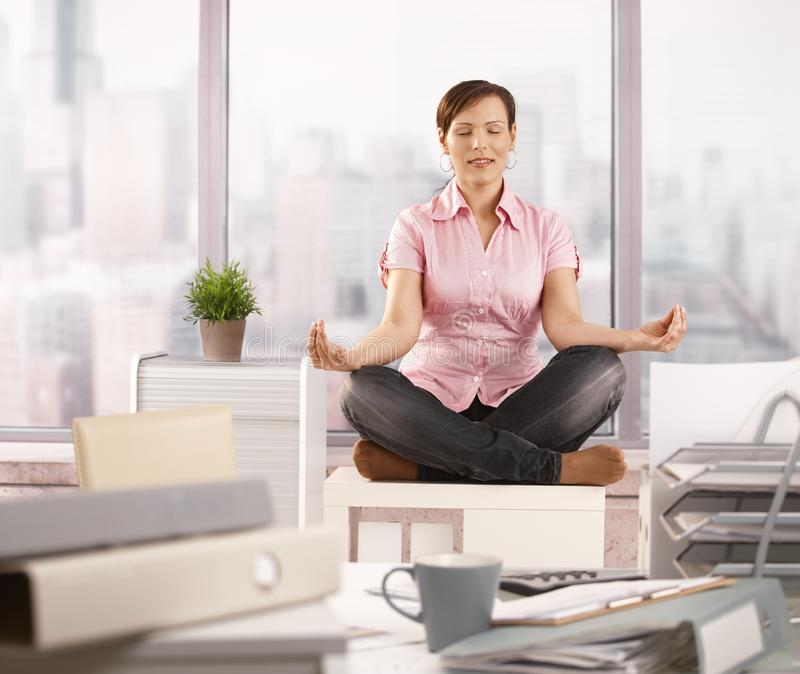 Relaxed office worker doing yoga stock photography