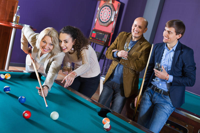Relaxed people playing billiard and darts as hanging out royalty free stock photography