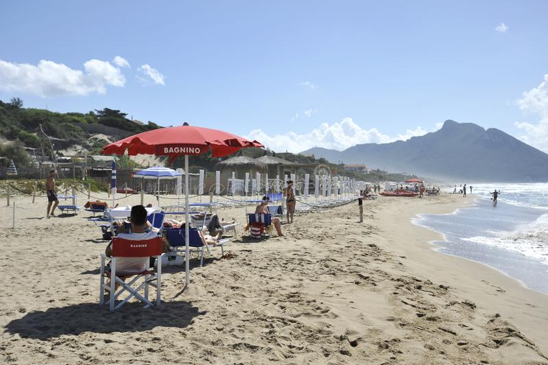 Relaxed people on the Sabaudia beach for the summer holidays. The lifeguard keeps watch and the Circeo Mountain is on the stock image