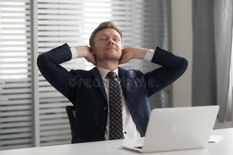 Relaxed positive mindful male manager having rest at office. royalty free stock photos
