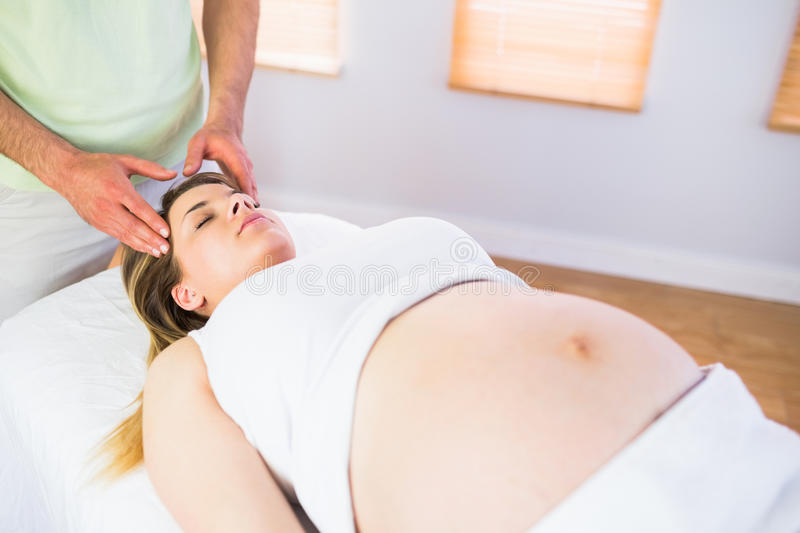 Relaxed pregnant woman enjoying head massage stock image
