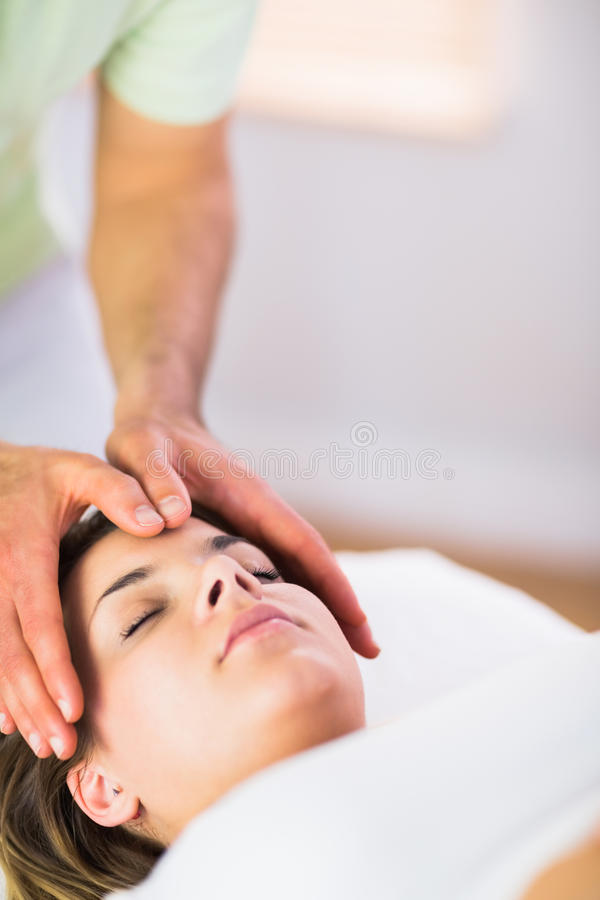 Relaxed pregnant woman getting reiki treatment stock photography