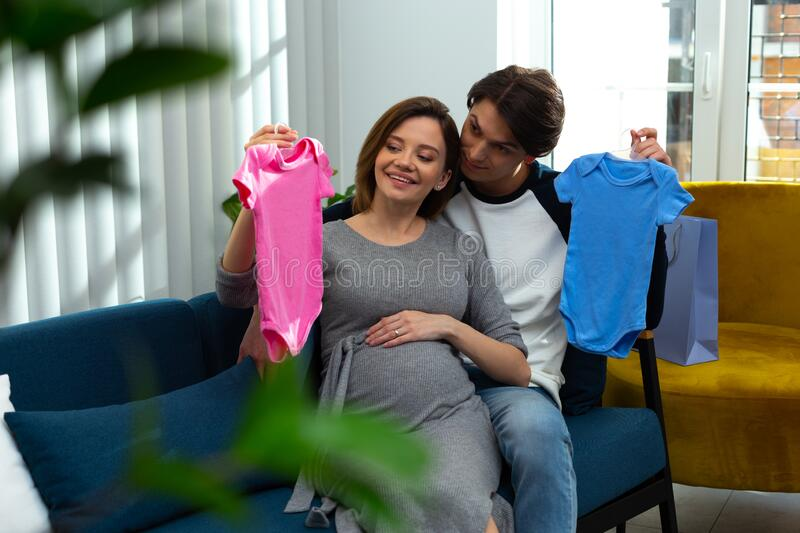 Happy couple expecting twins and preparing clothes for them stock images