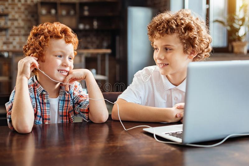 Relaxed redhead children listening to music at table. Calmness and serenity. Joyful curly haired boys sitting at a laptop while both listening to music playing stock photography