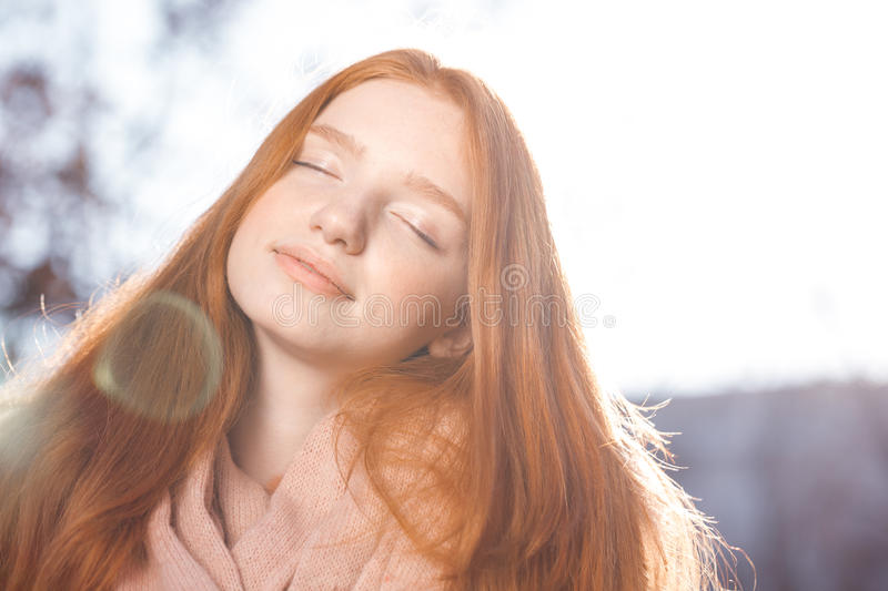 Relaxed redhead woman standing outdoors royalty free stock photography