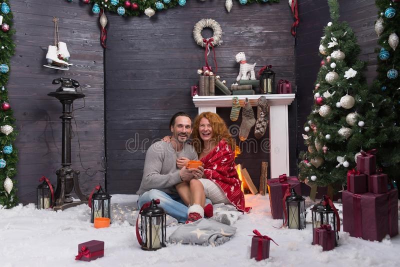 Full length of hugging couple sitting near the fireplace and smiling. Relaxed romantic couple enjoying New Year holidays and hugging near the fireplace on fluffy royalty free stock image